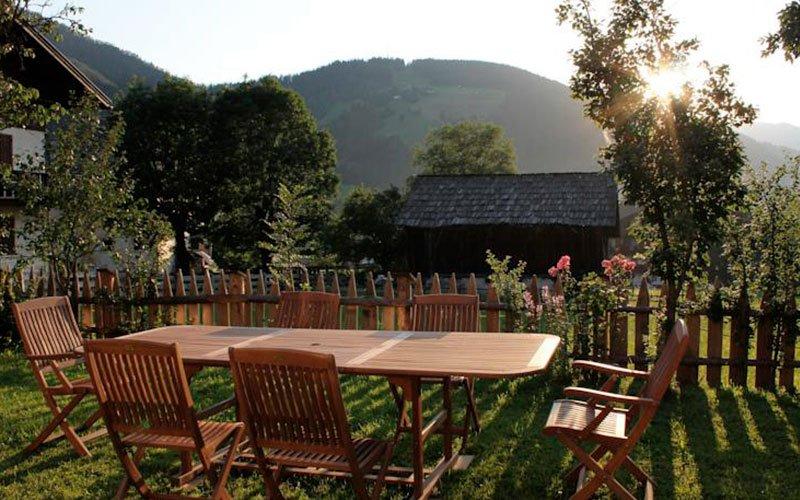 Bed and breakfast Ciasa Brüscia vista del giardino con tavoli e tramonto sulle montagne